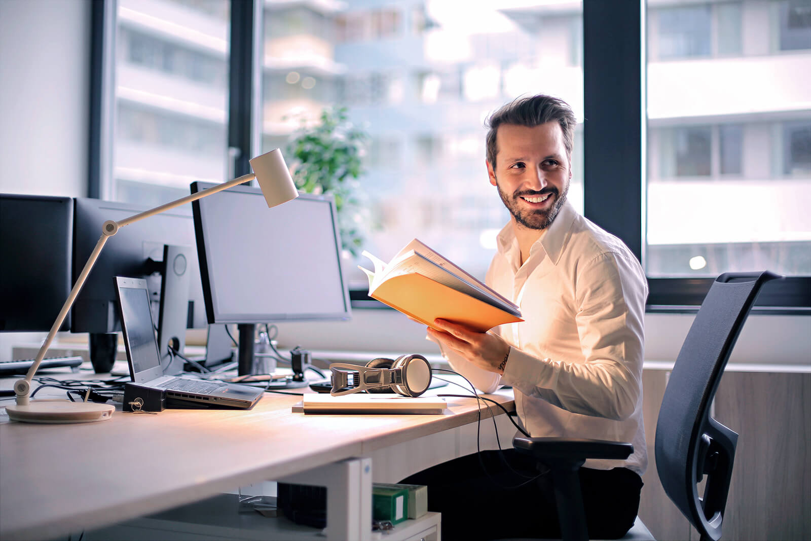 A man sitting at his desk in his office and really enjoying reading a handy Nxtbook guide