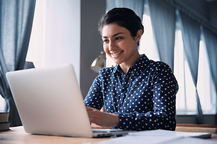 A woman smiles as she looks over her marketing plan from Nxtbook Media on her laptop