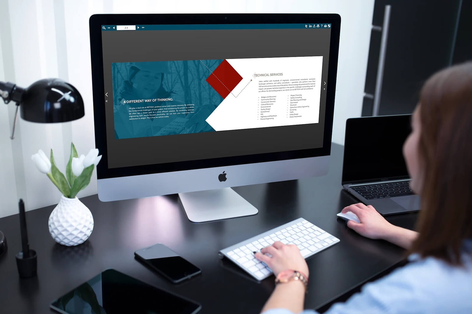 woman creating a digital brochure on an iMac