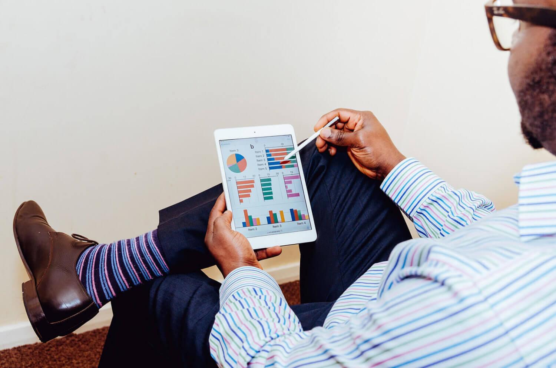 A man looks at graphs on an iPad